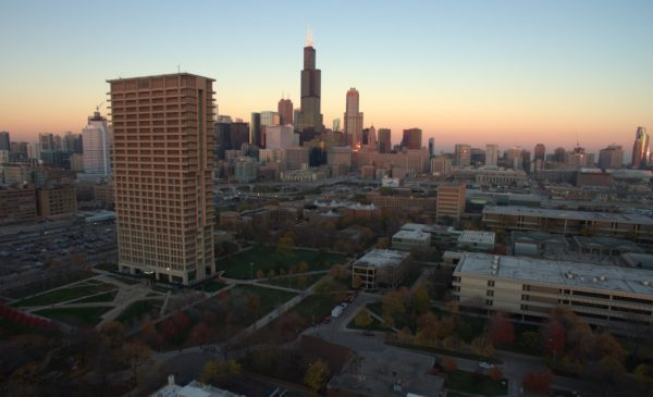 An aerial view of the Chicago skyline at dusk, with University Hall and UIC's East Campus in the foreground.