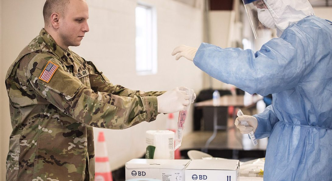 Illinois National Guardsmen bag a COVID-19 test at a drive-thru testing site in Bloomington, Ill.