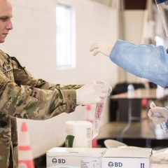 A COVID-19 test sample is processed by a member of the Illinois National Guard.