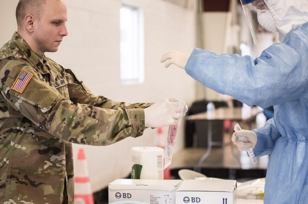 Two members of the Illinois National Guard prepare a COVID-19 test kit for processing.