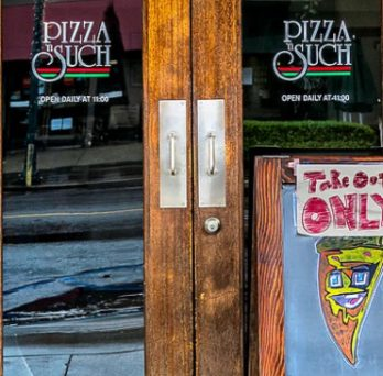 A pizza restaurant has a sign board outside that says