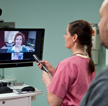 A telehealth consultation at a VA clinic, with a nurse adjusting a television set with a video feed from a doctor, as a patient waits in the background.