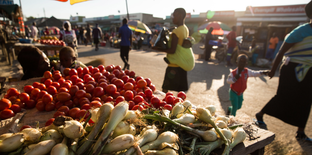 People walk past a table full of tomatoes and green onions at an outdoor market in Kisumu, Kenya.