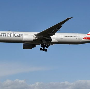 An American Airlines Boeing 777 plane flies in the sky.