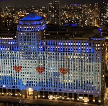 An aerial view of Merchandise Mart, lit up with a graphic of the Chicago flag and text stating