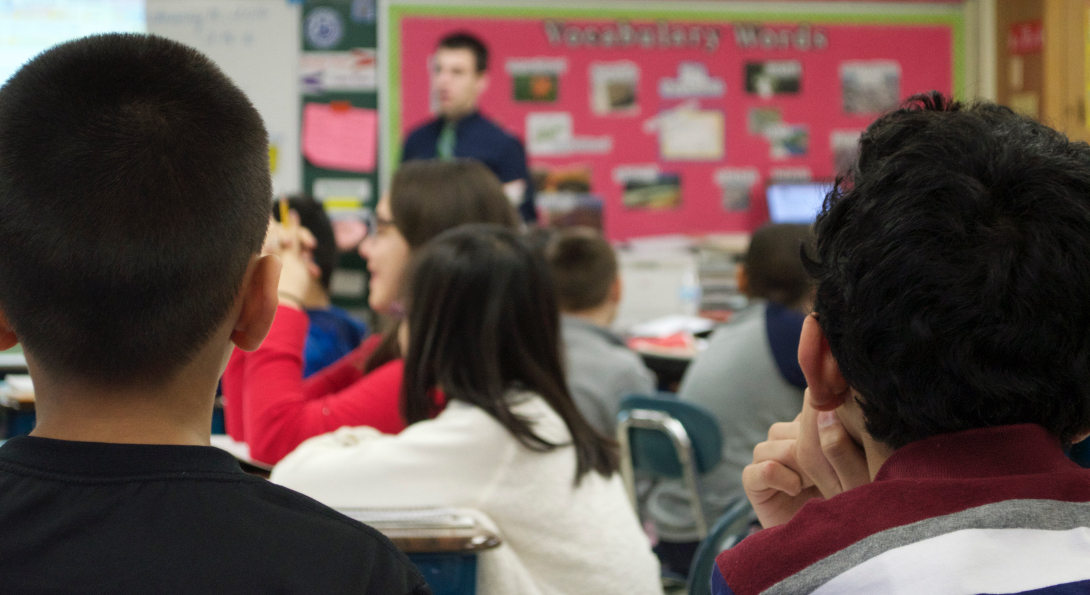 Teacher Michael Scaletta walks across the front of his classroom while speaking to his students.