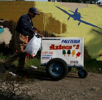 An ice cream vendor pushes his cart past a wall mural on a street in Little Village.