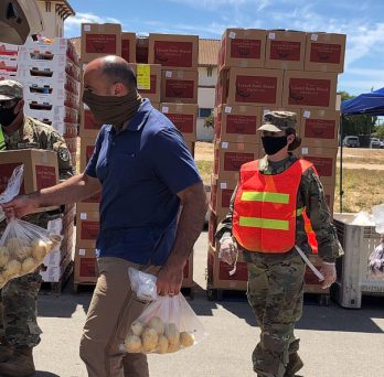 California National Guard members load potatoes into the back of a truck, with boxes of food stacked behind them.