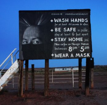 A sign posted on Navajo Nation territory reminds people to follow COVID-19 safety guidelines.