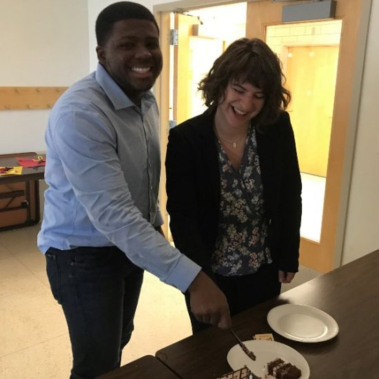 Two PMP participants grabbing a slice of cake.