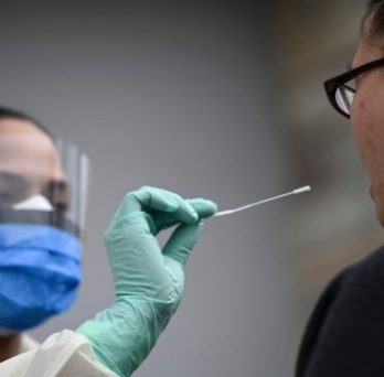 A medical professional prepares to perform a COVID-19 nasal swab test with a patient.