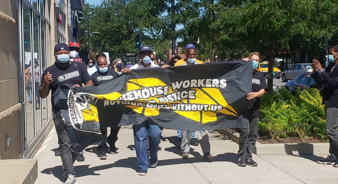 Warehouse workers march down a sidewalk wearing masks and holding a banner that says