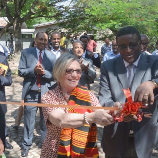 Mary Harvey cuts a ribbon at an opening ceremony at a health clinic.