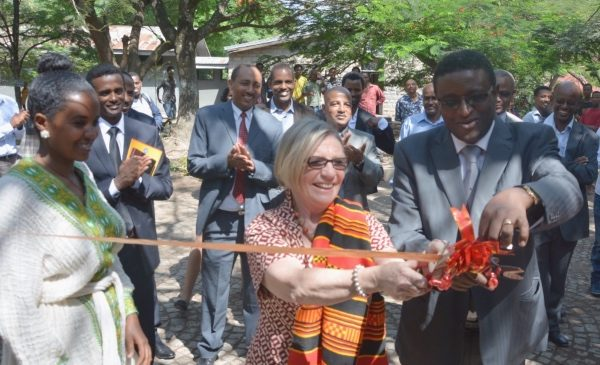 Mary Harvey cuts a ribbon as colleagues from Amhara University in Ethiopia look on.