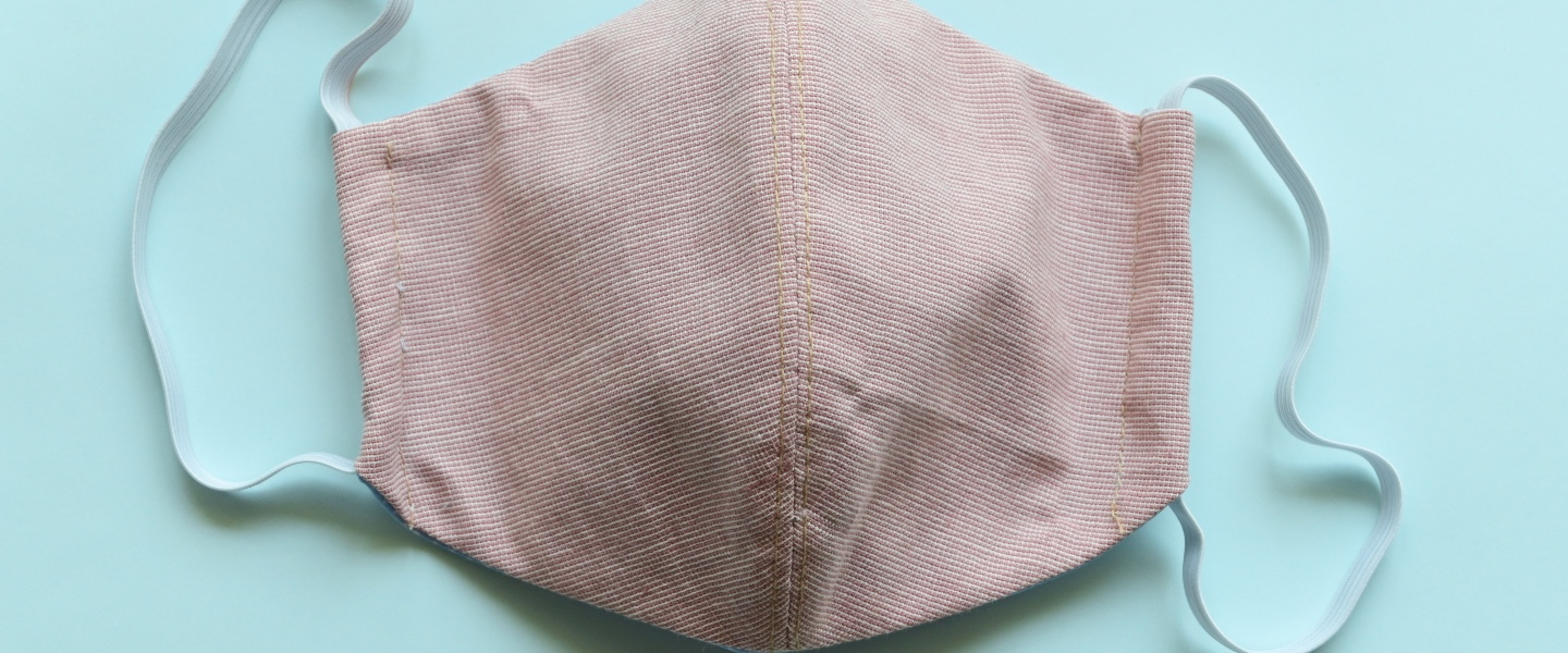A pink-colored cloth face mask, against a light blue-green background.