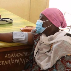 A patient at a healthcare clinic in Ghana has blood pressure checked.