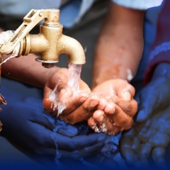 A person washes their hands from a spigot attached to a wooden post.