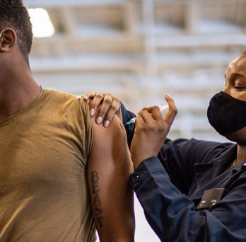 A patient receives an immunization via a shot to the shoulder area of their arm.