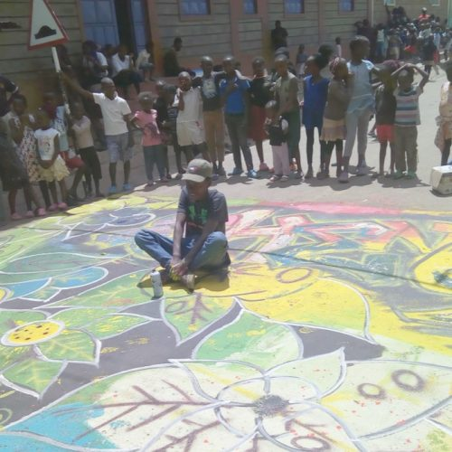 A child sits in a street atop a work of chalk art.
