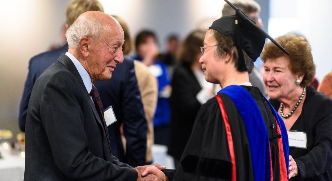 Dr. Samuel Epstein and Mrs. Catherine Epstein congratulate An Li.