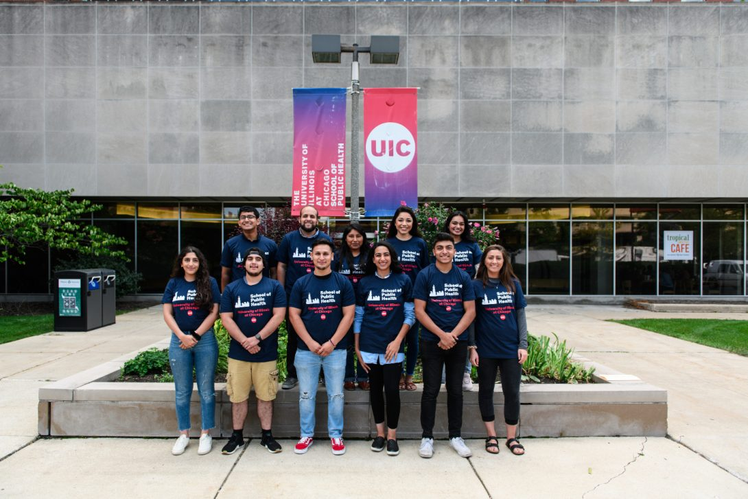 Undergraduate students posing outside of the School of Public Health buidling