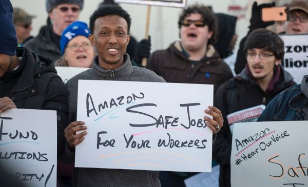 A group of workers hold signs while protesting outside an Amazon warehouse in Shakopee, Minnesota.