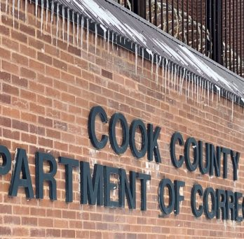 A sign on a brick wall for the Cook County Jail Department of Corrections.