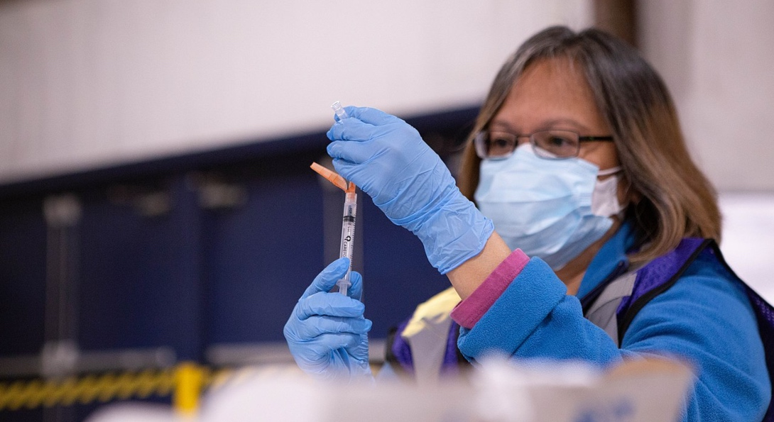 A medical professional fills a needle with the COVID-19 vaccine solution in preparation for an inoculation.