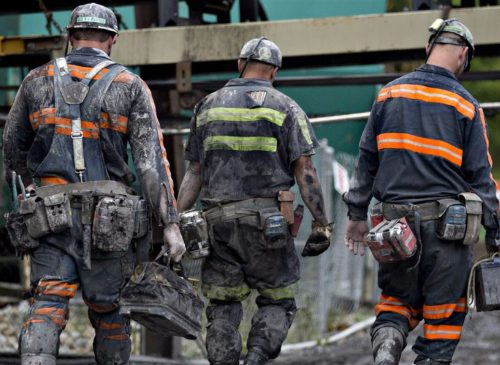 Coal miners walk together following a work shift.