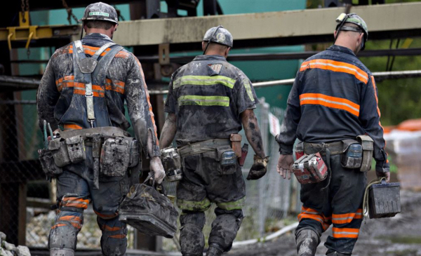 Coal miners walk together after a shift of work.