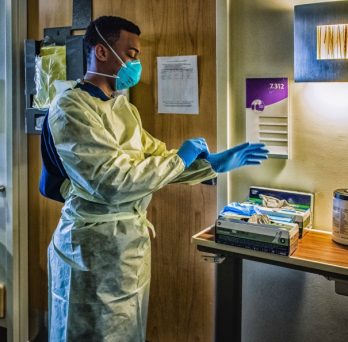 A medical professional dons full personal protective equipment before entering a hospital room with a COVID-19 patient.