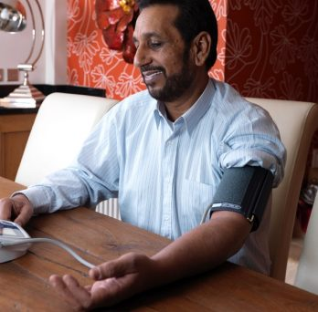 A man takes his own blood pressure using a telehealth device.