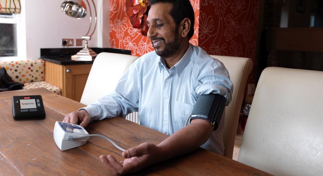 A man takes his own blood pressure using a telehealth device.