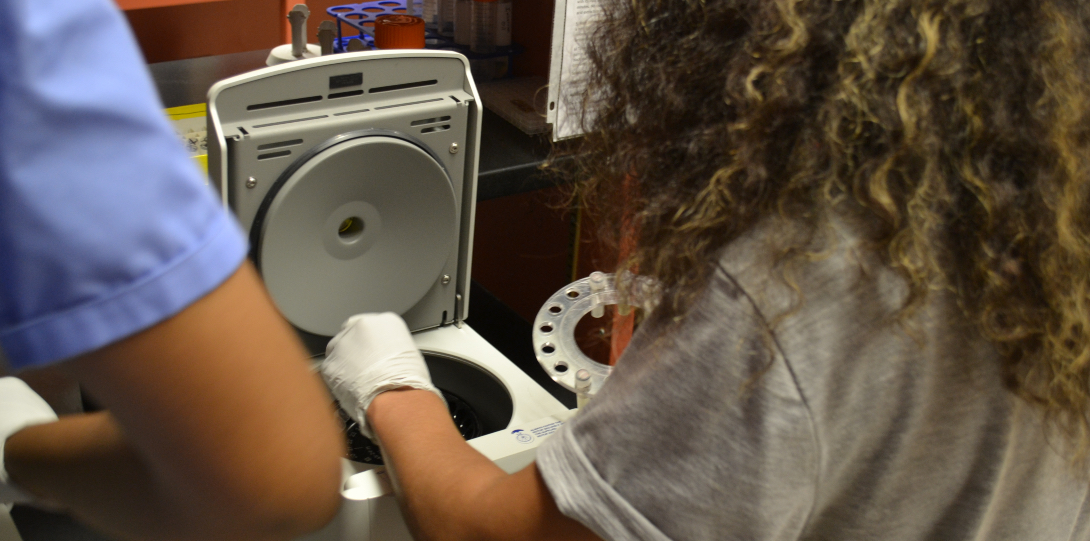 A lab technician loads water samples into a centrifuge.