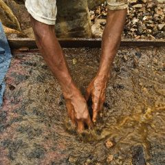 An artisanal gold miner sifts through silt in a large pan filled with water.
