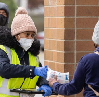 An outreach worker hands out masks to people at a Walgreens in the Mayfair neighborhood of Chicago.