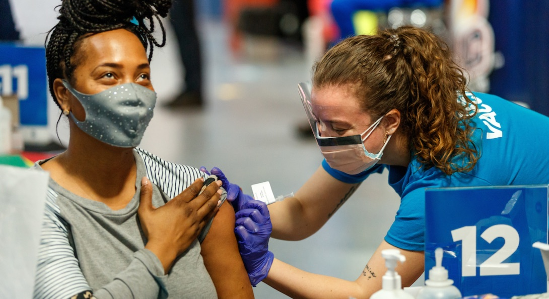 A Black woman is the recipient of a COVID-19 vaccine, injected into her left arm.