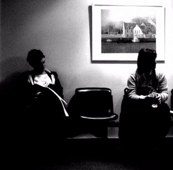 People sit in a doctor's office waiting room.