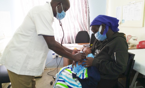 A doctor in Kenya examines a young infant male, who is in the arms of his mother.