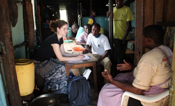 A student conducts a field interview with a family in Kisumu, Kenya, in their home.