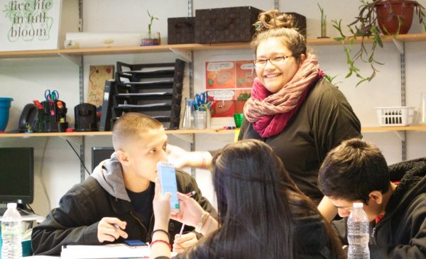 A teacher of Latina descent speaks to Latinx students in her classroom.