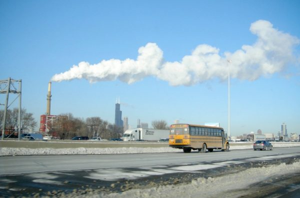 A school bus passes near the Crawford Generating Station, which is emitting a large cloud of white smoke.