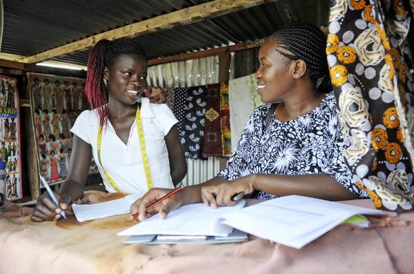 An adolescent girl in Kisumu completes a questionnaire with a researcher.