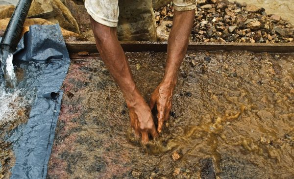 An artisanal miner sifts through silt combined with mercury in a water bath.
