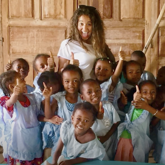 Hannah Bonecutter poses for a photo surrounded by a group of smiling children.