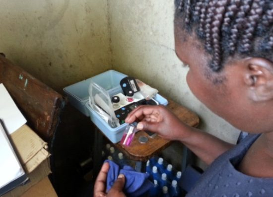 An MPH student examines water samples in small glass vials while abroad in Kenya.