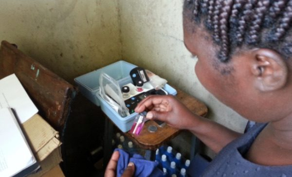 An SPH student in Kenya examines water purification samples in a vial.