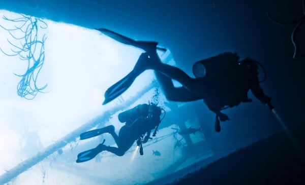 Divers explore the underwater side of a boat.