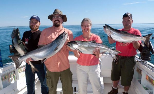 Charter boat customers hold up large fish they caught during their voyage.