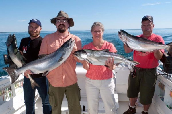 Charter boat passengers hold up fish they caught during their voyage.